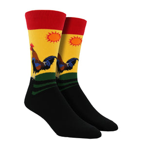 A rooster is seen standing on a farm fence greeting the morning on this yellow cotton crew sock for men by Socksmith.