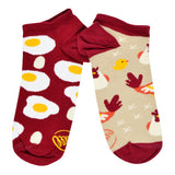These mismatched cotton ankle socks by the brand Many Mornings feature one socks that's tan with a maroon heel, toe and cuff that has chickens on it, and the other sock is maroon with fried eggs on it.
