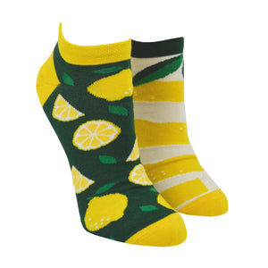 On a mannequin foot form, a pair of mismatched Many Mornings cotton socks are shown with one sock featuring whole and cut lemons while the other sock features a different lemon peel design.