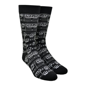 A black cotton Men's crew sock by Modsock is shown on a mannequin foot form featuring a sheet music design from its top to bottom.