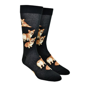 Shown on a leg form, these black cotton men's fun novelty crew socks by the brand Mod Socks feature adorable Corgi dogs smiling, sitting down and some standing up showing their cute butts.
