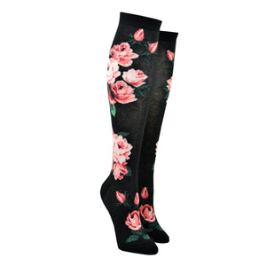 A pair of women's cotton knee high socks by Modsock feature bright pink roses on a black background and are shown on a mannequin leg form.