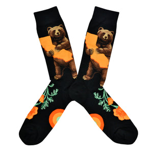 These black cotton men's crew socks by the brand Mod Socks feature a bear standing and hugging a large orange sketch of the state of California, and orange California poppy's on the foot.