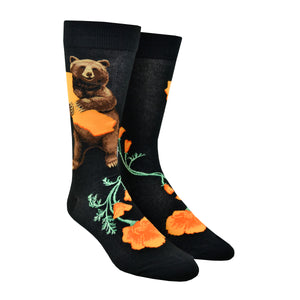 Shown on a leg form, these black cotton men's crew socks by the brand Mod Socks feature a bear standing and hugging a large orange sketch of the state of California, and orange California poppy's on the foot.