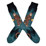 These heathered blue/green and black funny men's cotton crew socks by Mod Socks feature Big Foot walking amongst the trees drinking a beer.