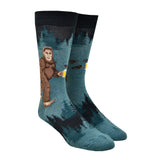 Shown on a leg form, these heathered blue/green and black funny men's cotton crew socks by Mod Socks feature Big Foot walking amongst the trees drinking a beer.