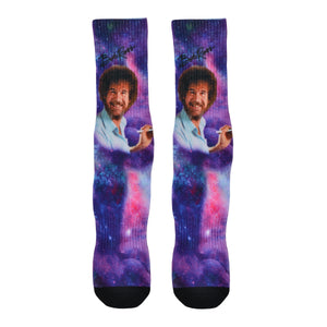 Famous artist Bob Ross is shown painting while floating through a galaxy background of this purple unisex cotton crew sock by Good Luck socks.