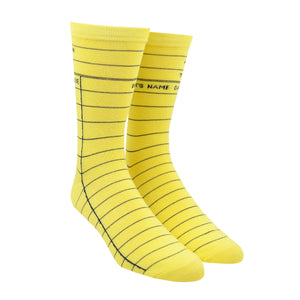 "Shown on a leg form in the men's size, these yellow cotton unisex crew socks by the brand Out of Print feature the iconic library card design with the words ""Author, Title, Date Due"" written on the leg and a grid for filling in the information running down the leg and foot."