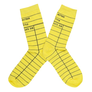 "These yellow cotton unisex crew socks by the brand Out of Print feature the iconic library card design with the words ""Author, Title, Date Due"" written on the leg and a grid for filling in the information running down the leg and foot."