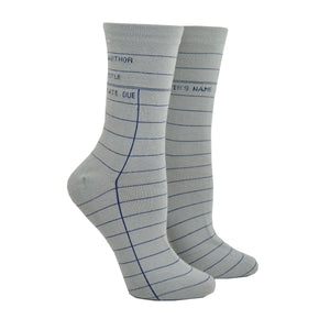 "Shown on a leg form in the women's size, these gray cotton unisex crew socks by the brand Out of Print feature the iconic library card design with the words ""Author, Title, Date Due"" written on the leg and a grid for filling in the information running down the leg and foot."