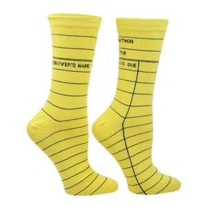 "A side view shown on a leg form in the women's size, these yellow cotton unisex crew socks by the brand Out of Print feature the iconic library card design with the words ""Author, Title, Date Due"" written on the leg and a grid for filling in the information running down the leg and foot."