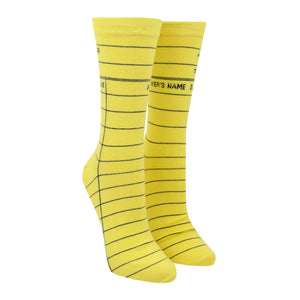 "Shown on a leg form in the women's size, these yellow cotton unisex crew socks by the brand Out of Print feature the iconic library card design with the words ""Author, Title, Date Due"" written on the leg and a grid for filling in the information running down the leg and foot."