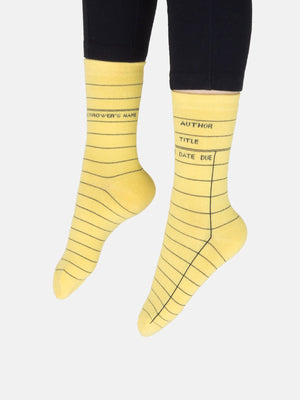 "A model wearing yellow cotton unisex crew socks by the brand Out of Print feature the iconic library card design with the words ""Author, Title, Date Due"" written on the leg and a grid for filling in the information running down the leg and foot."