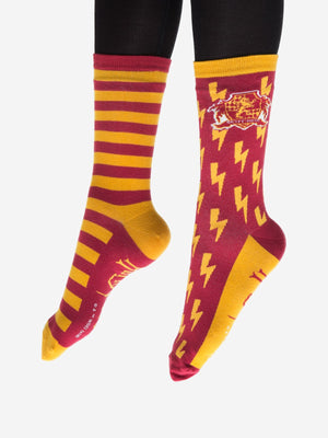 A model wearing red and yellow unisex novelty socks by the brand Out of Print feature the Harry Potter house crest for Gryffindor in front of lightening bolds on one sock and stripes on the other.