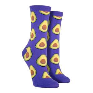 Shown on a leg form, these purple cotton women's novelty crew socks by the brand Socksmith feature light green avocados sliced in half showing their brown pits.