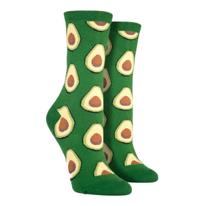 Shown on a leg form, these green cotton women's novelty crew socks by the brand Socksmith feature light green avocados sliced in half showing their brown pits.