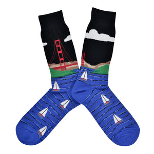These black cotton men's crew socks by the brand Socksmtih feature the iconic landmark of San Francisco, the Golden Gate Bridge, towering above the beautiful blue San Francisco Bay filled with sailboats.