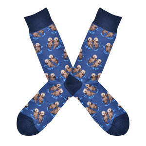 These blue cotton men's crew socks with a navy heel, toe and cuff by the brand Socksmith feature adorable otters floating in the ocean holding hands.