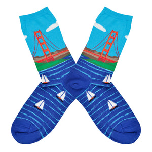 These blue cotton women's crew socks by the brand Socksmtih feature the iconic landmark of San Francisco, the Golden Gate Bridge, on a clear sunny day towering above the beautiful bay filled with sailboats.