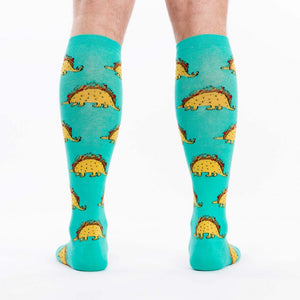 A model wearing blue cotton unisex knee high socks by the brand Sock It To Me featuring dinosaurs with bodies that look like a taco.