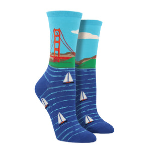 Shown on a leg form, these blue cotton women's crew socks by the brand Socksmtih feature the iconic landmark of San Francisco, the Golden Gate Bridge, on a clear sunny day towering above the beautiful bay filled with sailboats.