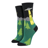"Shown on a leg form, these black cotton women's crew socks by the brand Socksmith feature an alien spaceship hovering over pine trees in front of a gray mountain, abducting a person as they shout ""Take me away!"""
