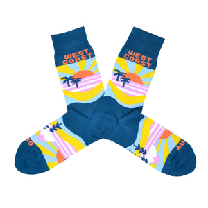 "These blue cotton men's novelty crew socks by the brand Yellow Owl Workshop feature an orange and yellow sun setting over a pink landscape with blue palm trees and say the words ""West Coast Best Coast"" near the cuff and ""Stay Gold"" by the toes."