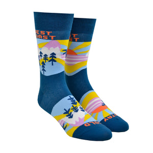 "Shown on a leg form, these blue cotton men's novelty crew socks by the brand Yellow Owl Workshop feature an orange and yellow sun setting over a pink landscape with blue palm trees and say the words ""West Coast Best Coast"" near the cuff and ""Stay Gold"" by the toes."