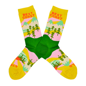 "These yellow cotton women's novelty crew socks by the brand Yellow Owl Workshop feature green trees, teal and white mountains, and pink clouds and say the words ""West Coast Best Coast"" near the cuff and ""Stay Gold"" by the toes."
