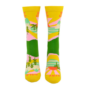 "A front view on a leg form, these yellow cotton women's novelty crew socks by the brand Yellow Owl Workshop feature green trees, teal and white mountains, and pink clouds and say the words ""West Coast Best Coast"" near the cuff and ""Stay Gold"" by the toes."