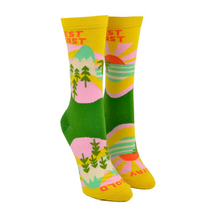 "Shown on a leg form, these yellow cotton women's novelty crew socks by the brand Yellow Owl Workshop feature green trees, teal and white mountains, and pink clouds and say the words ""West Coast Best Coast"" near the cuff and ""Stay Gold"" by the toes."