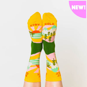 "A model wearing yellow cotton women's novelty crew socks by the brand Yellow Owl Workshop feature green trees, teal and white mountains, and pink clouds and say the words ""West Coast Best Coast"" near the cuff and ""Stay Gold"" by the toes."