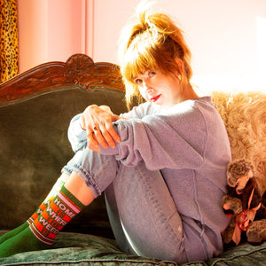 "A model wearing green cotton unisex crew socks with an orange and pink striped toe and cuff by the brand Gumball Poodle feature the words ""HOME IS WHERE THE WEED IS"" on the leg."