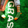 "A model wearing green cotton unisex crew socks with an orange and pink striped toe and cuff by the brand Gumball Poodle feature the words ""HOME IS WHERE THE WEED IS"" on the leg while sitting on a carpet that says ""GRASS""."