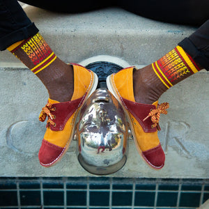 "A model wearing brown cotton unisex crew socks with a yellow and red striped toe and cuff by the brand Gumball Poodle feature the word ""WHISKEY"" repeated down the leg in yellow, orange and red writing."
