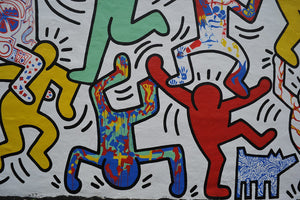 The 1980's street culture pop artwork of Keith Haring, showing his iconic outlines of dancing people in red, yellow, green and paint splatter.