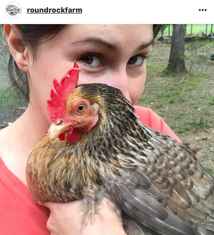 woman snuggling chicken