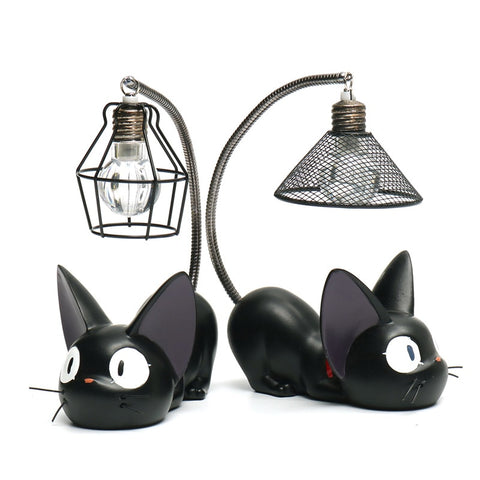 Lamp Hanging on a Small Black Cat