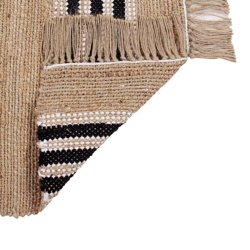 Handwoven jute rug with black and white stripes  and tassels at the end.