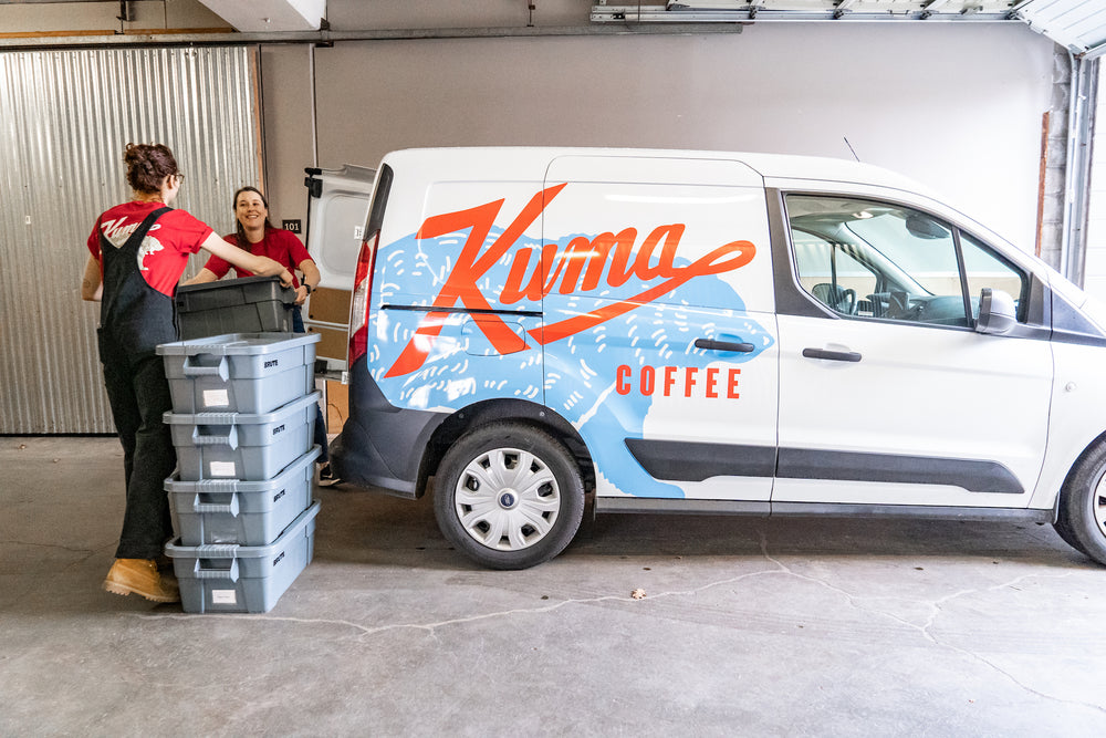 Two women wearing red bear t-shirts with a logo for Kuma Coffee smiling and lifting bins into the back of a van with the Kuma Coffee logo over a large blue bear on the side