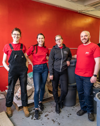 Team at Kuma Coffee smiling in Red Bear Kuma shirts and posing with coffee roasted for the day