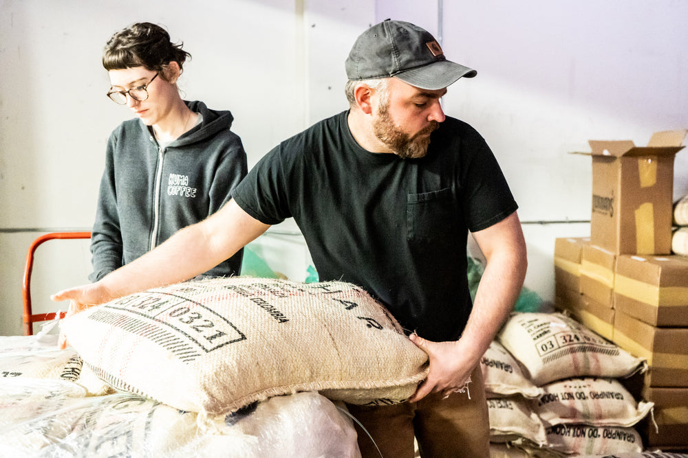 Man and woman wearing Kuma Coffee sweatshirt hard at work lifting burlap bags filled with Colombian coffee