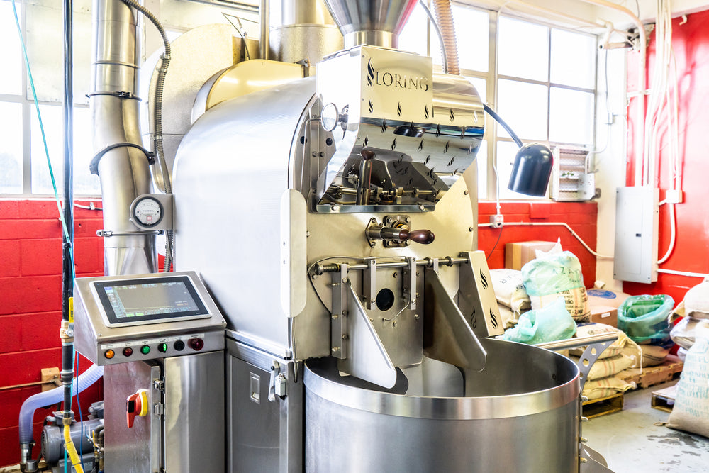 A Loring Kestrel 35 kilo coffee roasting machine in the Kuma Coffee seattle roastery with red walls and coffee bags in the background