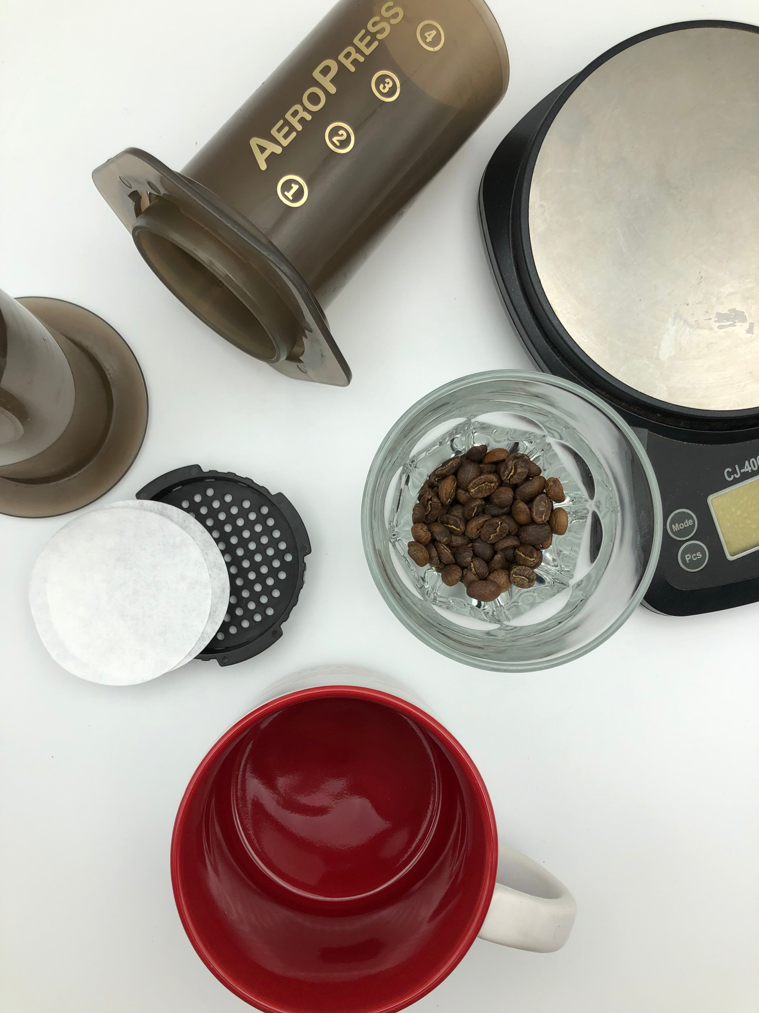 Tools needed to brew coffee in an aeropress including aeropress and filters, kettle, scale, red bear mug and Kuma Coffee