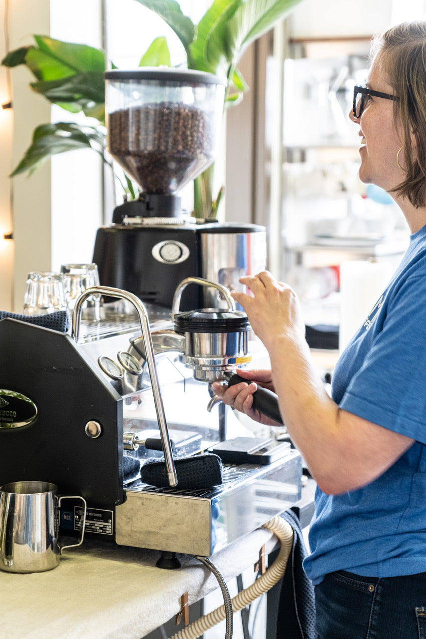 Woman smiling and making espresso in a light blue Kuma Coffee bear shirt