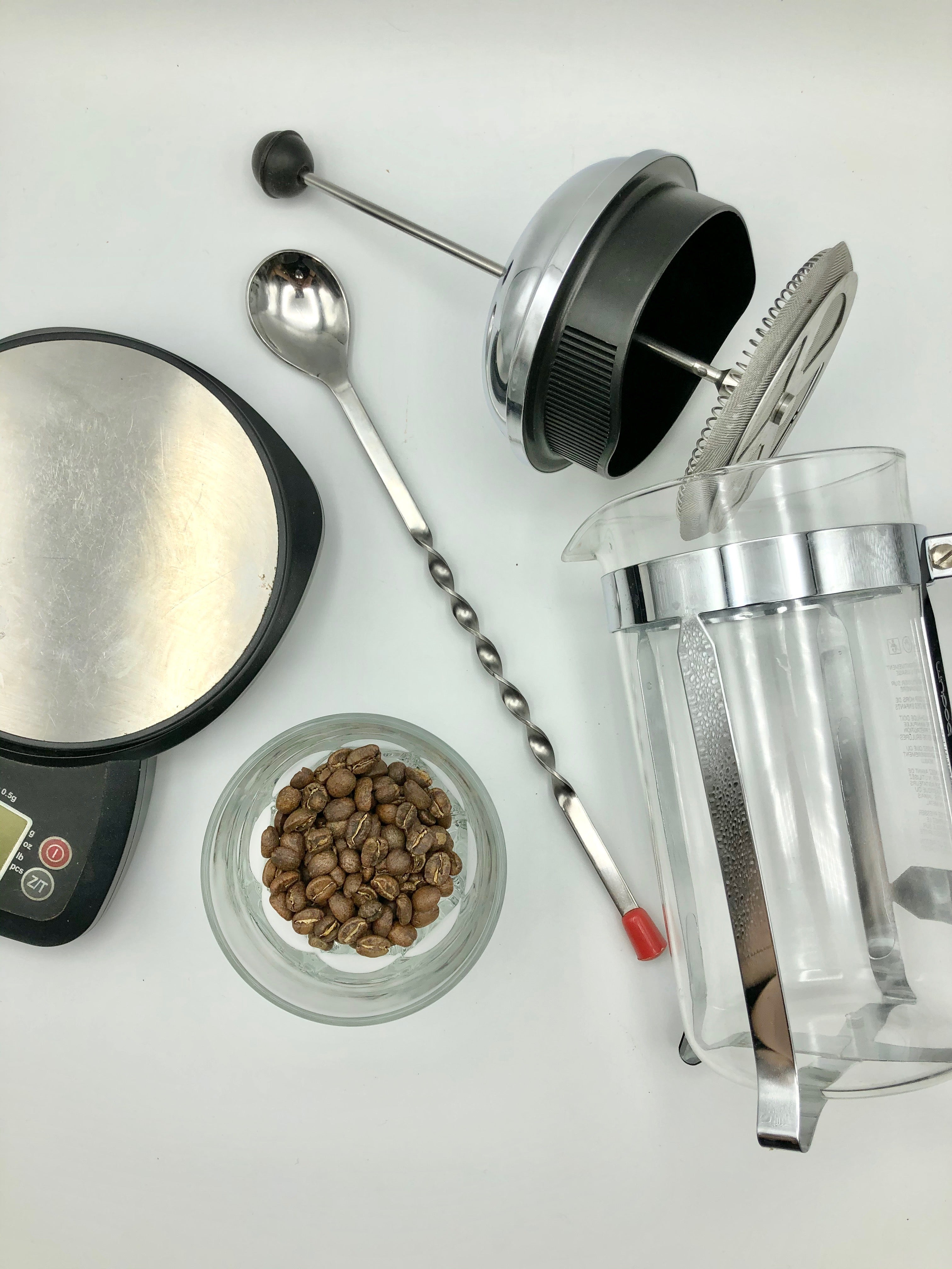 Tools needed to brew coffee in a french press, scale, coffee, spoon for stirring and french press