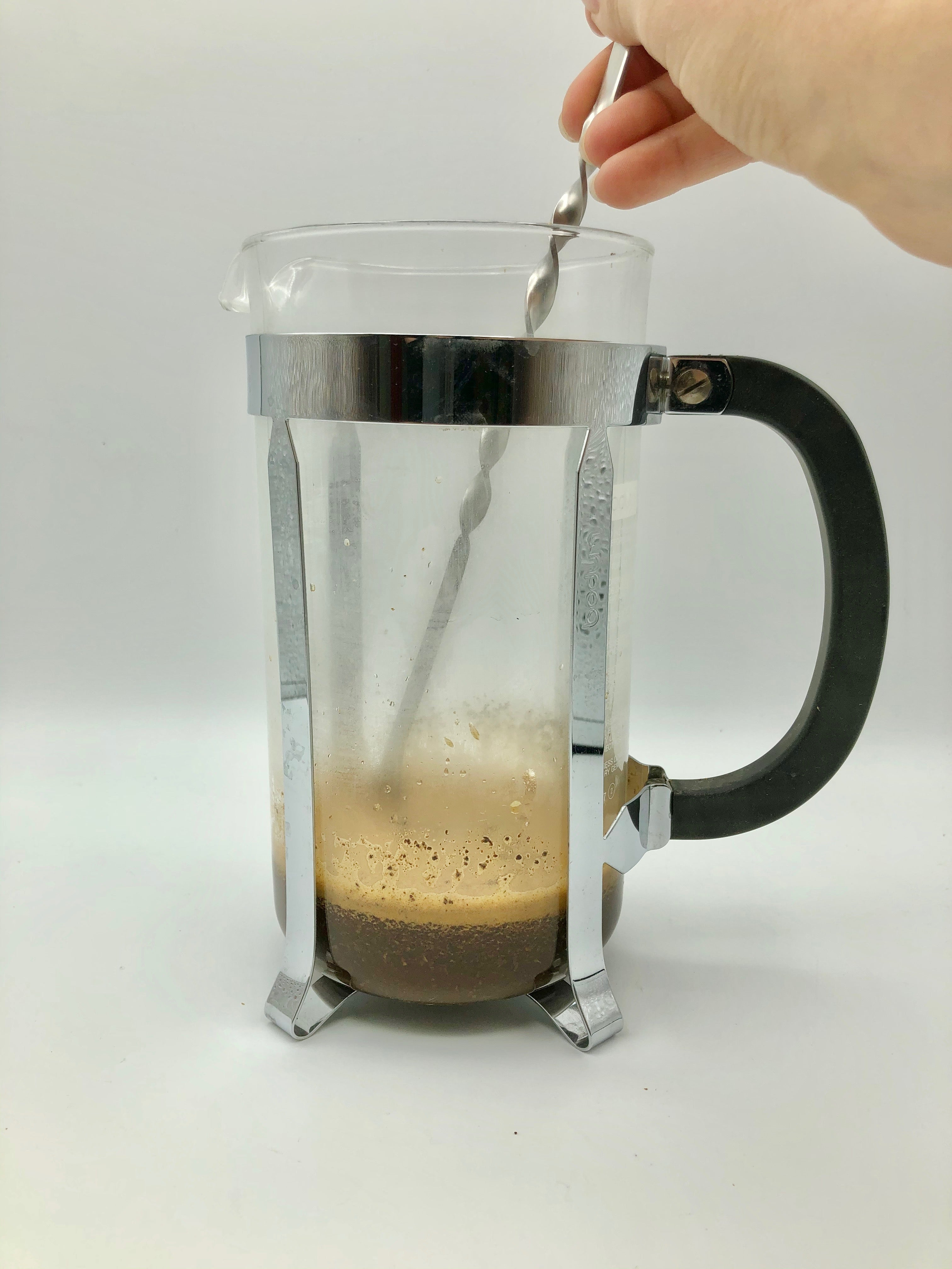 woman's hand string blooming coffee in a French Press