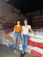 Two women smiling and leaning on bags of parchment coffee to be purchased and further processed