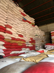 Large warehouse filled to the top with bags of parchment coffee waiting for further processing