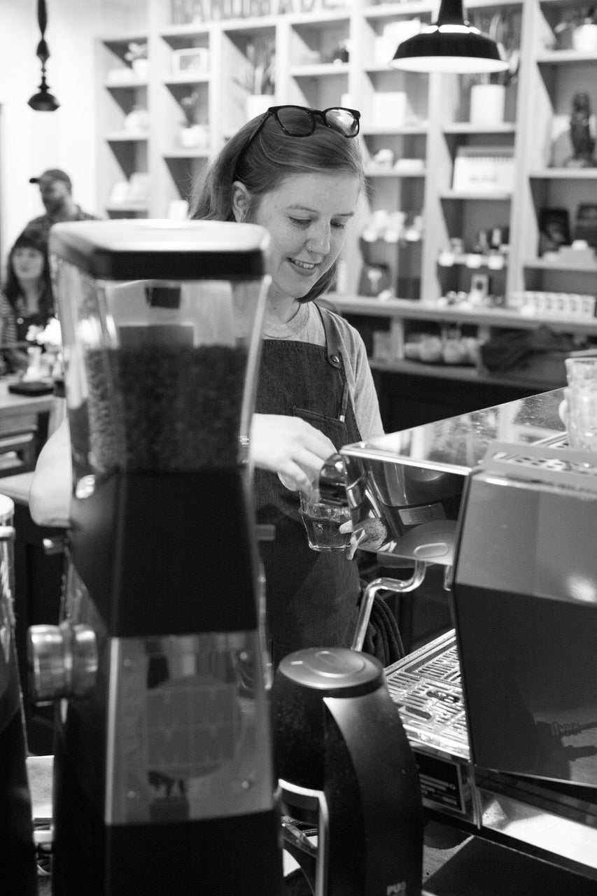 Accounts manager for Kuma Coffee smiling while making espresso on a La Marzocco Machine